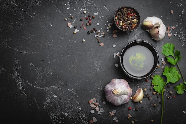 전통적인 요리 재료의 클로즈업:마늘, 올리브 오일, 소금, 후추, 어두운 소박한 배경에 신선한 허브. 음식 프레임, 텍스트를 위한 공간이 있는 건강한 음식 요리 개념, 위쪽 전망