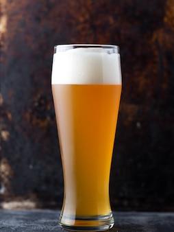 クローズ-ろ過されていない小麦ビールの伝統的な完全なガラスのクローズアップ