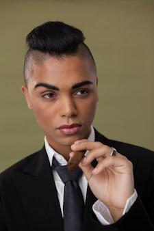 Крупным планом трансгендерной женщины, держащей сигарету