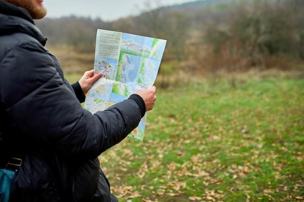 Крупным планом путешественника с рюкзаком с картой в руке на фоне горной реки природы