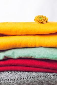 트렌디한 색상의 추운 날씨 옷, 가을, 겨울 스웨터의 클로즈업. 빨강, 초록, 노랑의 층이 서로 겹겹이 쌓여 있습니다. 색색의 따뜻한 옷 더미입니다.