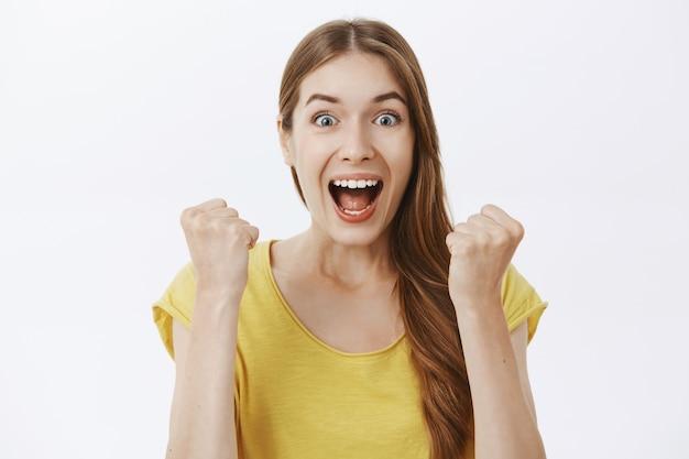 Крупный план торжествующей и радующейся счастливой женщины, выигравшей приз