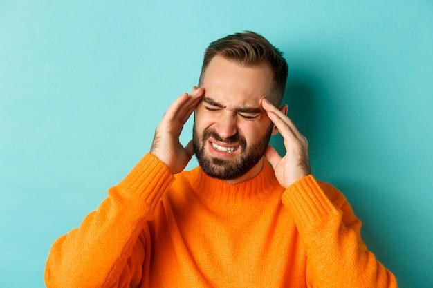 Крупный план обеспокоенного человека с головной болью, гримасой и касанием головы, страдающего мигренью, стоящего на голубом фоне.