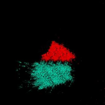 검은 배경에 청록색과 붉은 가루의 근접 촬영