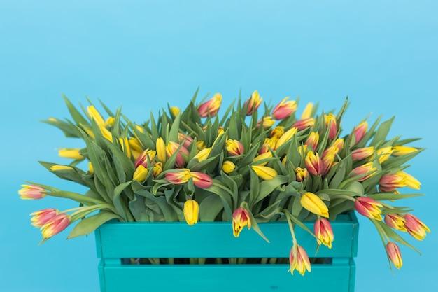 Крупным планом бирюзовый деревянный ящик с желтыми тюльпанами на синем фоне