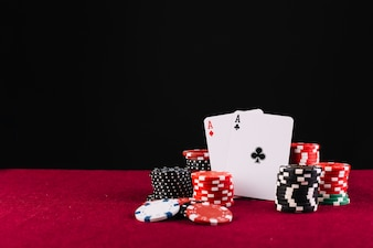 Close-up of two aces playing cards and poker chips on red background
