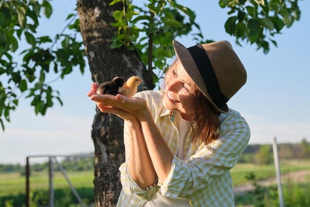 여자 손에 두 아기 병아리 닫습니다. 신생아 닭 노란색과 검은색 함께, 하늘 자연 배경