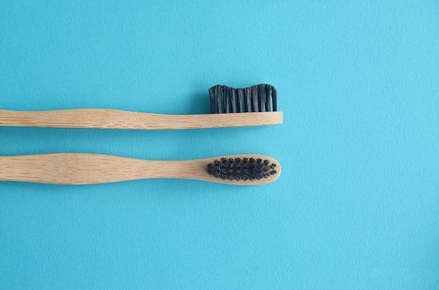 Крупным планом двух бамбуковых зубных щеток на синем фоне