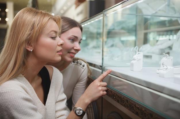 Крупным планом двух красивых женщин, выбирающих украшения для покупки в розничной торговле