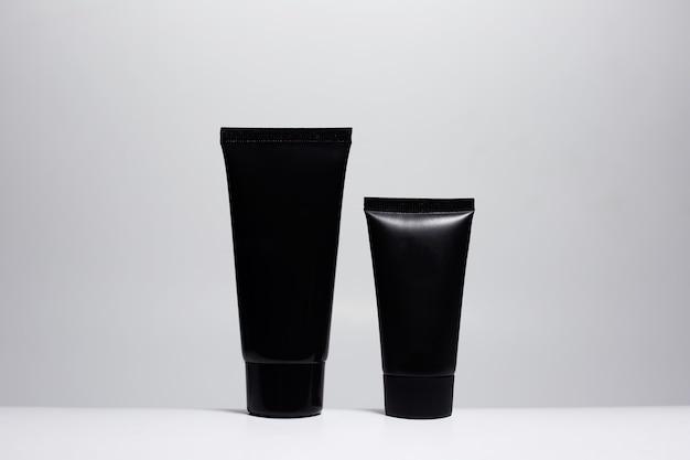 白い表面に分離された2つの黒いクリームチューブのクローズアップ