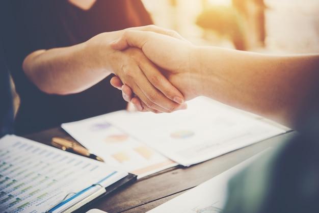 働く場所に座っている間に手を振る2つのビジネス人々のクローズアップ。