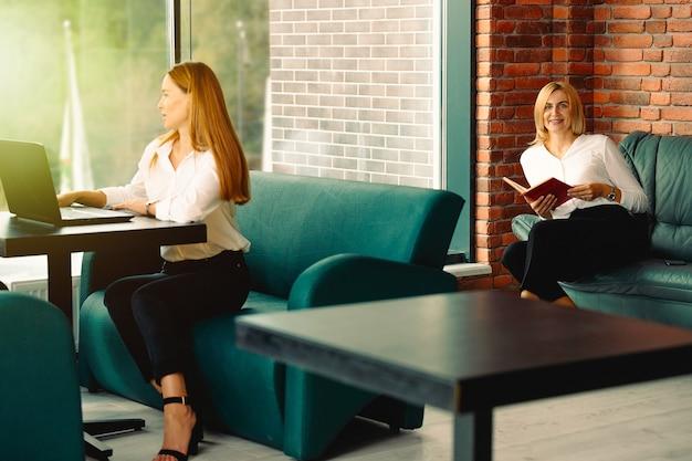 ノートパソコンを使用して休憩中に本を読んでいる2人の実業家のクローズアップ。ビジネスと財務の概念。人とライフスタイルのコンセプト。職場でのモダンなオフィスデザイン。