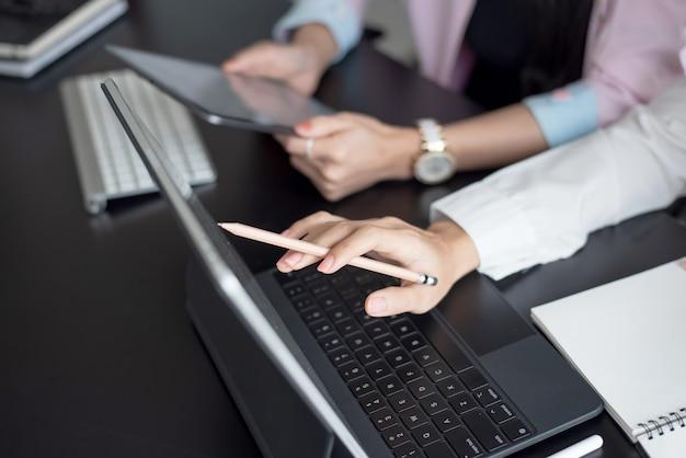 会議でデジタルタブレットを使用して2人のビジネスウーマンのクローズアップ