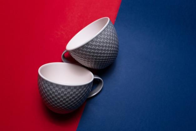 빨간색과 파란색 질감 된 벽에 두 세라믹 컵의 클로즈업.