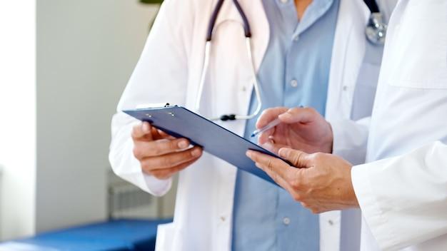 患者カードを保持している2人の医師の手のクローズアップ