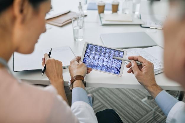 会議室の医療評議会中にx線画像を見ている2人の医師のクローズアップ、コピースペース