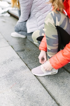 Close-up of two female runner tying shoelace