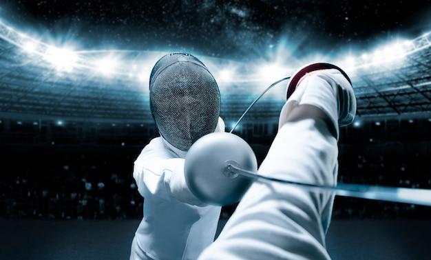 Крупным планом двух фехтовальщиков, занимающихся соревновательными видами спорта