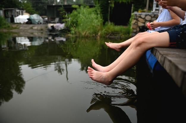 暖かい夏の日に、男の子と女の子、兄と妹の2人の友人のクローズアップが桟橋に座って、水に足をぶら下げ、前景に飛び散っています。