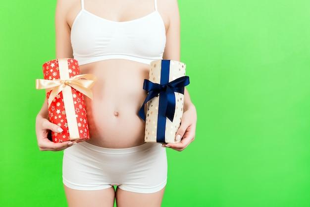 녹색 배경에서 그녀의 배꼽에 대 한 임신한 여자의 손에 두 개의 선물 상자를 닫습니다. 소년인가 소녀인가? 쌍둥이를 기다립니다. 공간을 복사합니다.