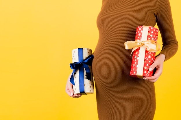 노란색 배경에서 그녀의 배꼽에 대 한 임신한 여자의 손에 두 개의 선물 상자를 닫습니다. 소년인가 소녀인가? 쌍둥이를 기다립니다. 공간을 복사합니다.