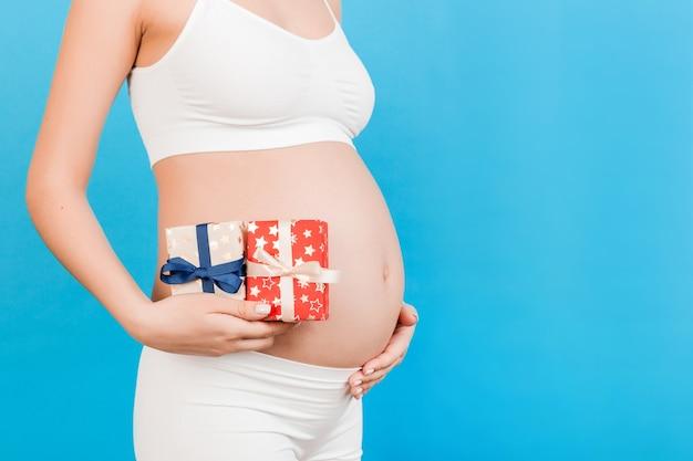 파란색 표면에서 그녀의 배꼽에 임신 한 여자의 손에 두 개의 선물 상자 닫습니다