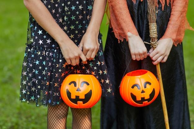 Крупный план двух девушек, держащих корзины в виде тыквы для сладостей на открытом воздухе