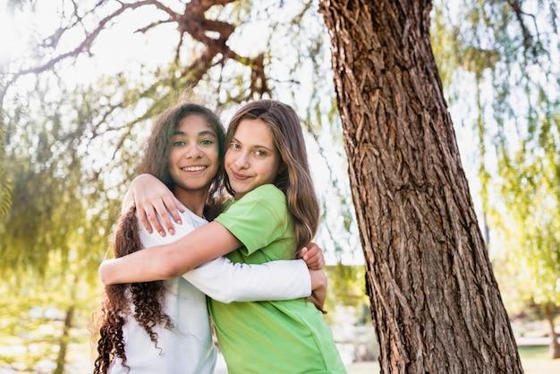 Крупным планом двух девушек, стоящих под деревом, обнимая друг друга