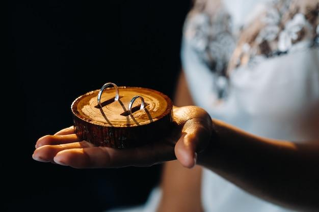 結婚式のための2つの金の結婚指輪のクローズアップは手にあります。