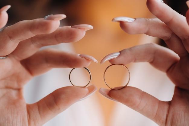 あなたの手の2つの金の結婚指輪のクローズアップ。