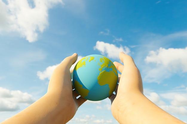 ぼやけた雲の背景と惑星地球を保持している2つの手のクローズアップ。 3dレンダリング