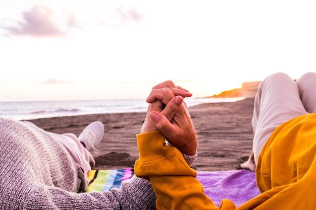 여름을 즐기고 함께 즐거운 시간을 보내는 배경에서 일몰과 함께 해변에서 함께 잡고 있는 두 손을 닫습니다. 모래 위의 커플