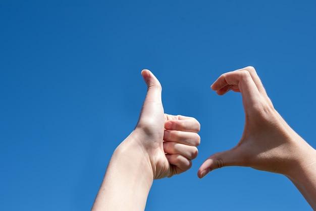 엄지손가락을 위로 올리는 두 손의 클로즈업, 파란색 배경에 하트 반쪽, 복사 공간. friendzone 개념, 낭만적 인 관계, 유혹