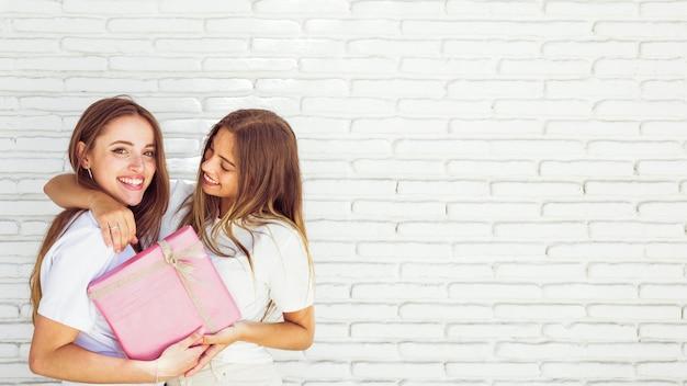 Крупный план двух счастливых женщин-друзей с подарком на день рождения