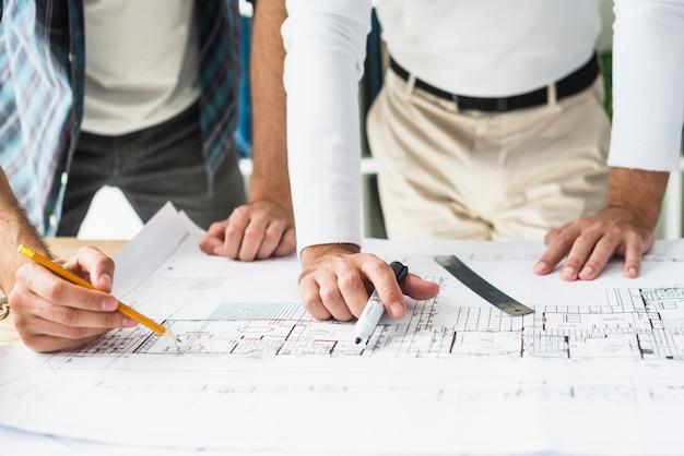 Крупный план рука двух мужчин-архитекторов над планом