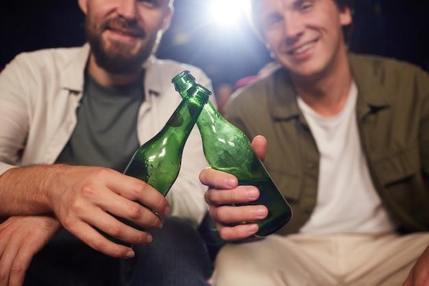 미소하고 시네마 극장에서 영화를 보는 동안 맥주 병을 부딪 치는 두 남자 친구의 닫습니다, 복사 공간