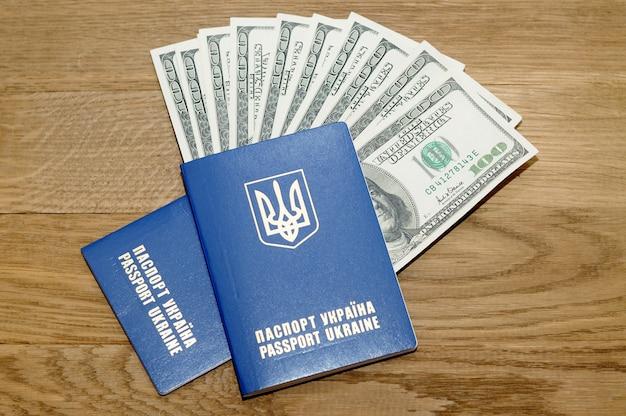 Закройте два паспорта и наличные деньги на деревянном столе