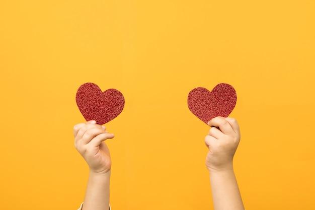 두 개의 붉은 심장 모양의 손에 닫습니다. 사랑과 발렌타인 데이 축하 개념.