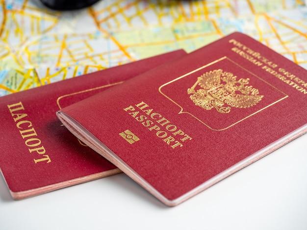 街の地図上に横たわっている2つのロシアのパスポートのクローズアップ。旅行と移住の概念