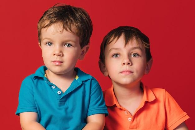 Крупный план двух мальчиков-братьев, изолированных на красном фоне.