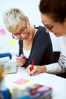 Закройте двух улыбающихся инновационных стильных деловых женщин среднего возраста, работающих вместе над решением проблем, сидя в офисе одна рядом с другой.