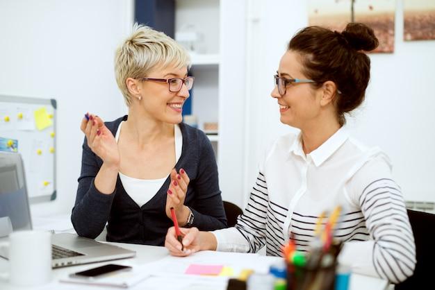 Закройте двух улыбающихся стильных деловых женщин среднего возраста, работающих и разговаривающих, сидя в офисе один рядом с другим.