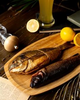 Крупным планом двух копченых рыб, служил в бамбуковой тарелке