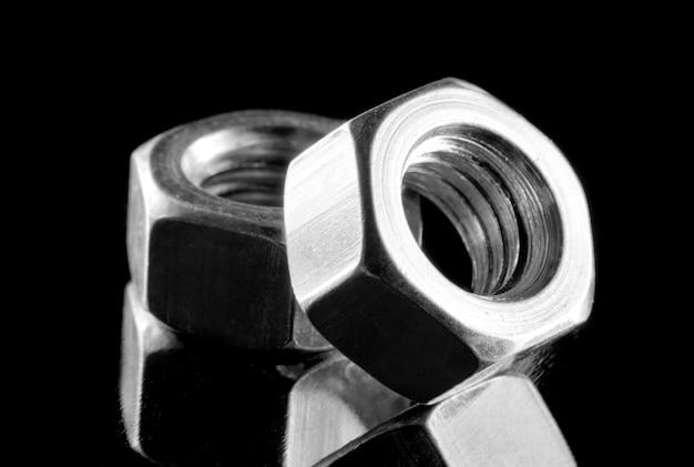두 개의 강철 너트의 클로즈업입니다. 흑백에서