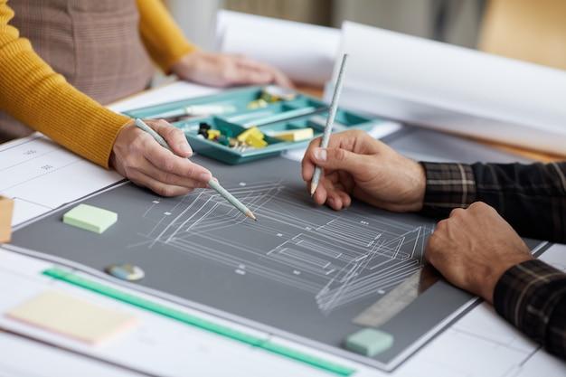 직장에서 청사진을 작업하는 동안 평면도를 가리키는 두 명의 인식 할 수없는 건축가의 닫습니다,