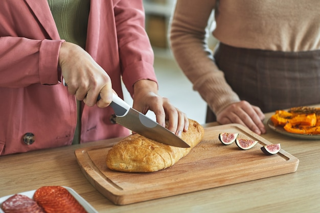 ディナーパーティーのために料理をしながら焼きたてのパンを切る2人の認識できない女性のクローズアップ、