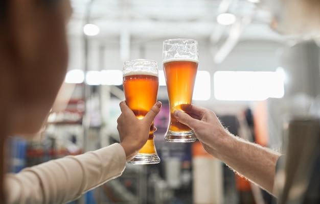醸造所、コピースペースでの生産とろ過の品質を検査しながらビアグラスを持っている2人の労働者のクローズアップ