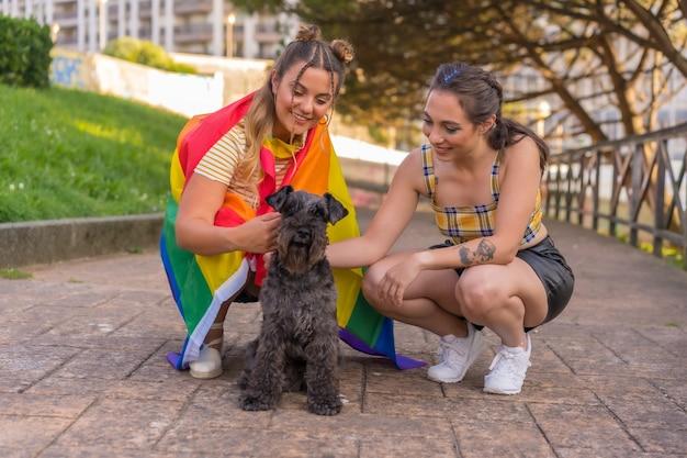 Крупный план двух молодых кавказских женщин, держащих флаг гордости лгбт в парке рядом с их черной собакой