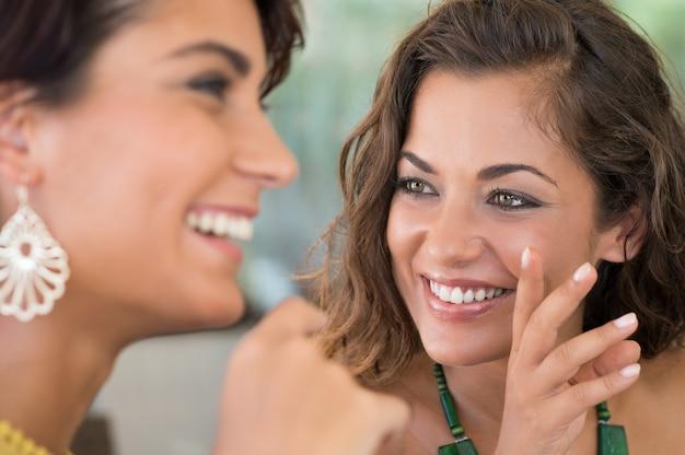 ゴシップについて互いに話している2人の若い女性のクローズアップ