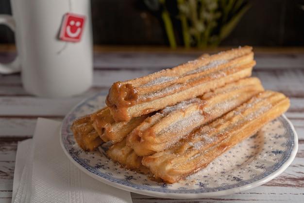 오래된 보드에 있는 빈티지 접시에 덜세 드 레체로 가득 찬 전형적인 히스패닉 츄로스의 클로즈업.